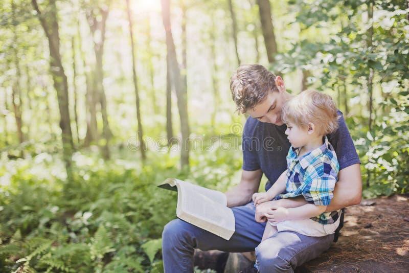 Bible de lecture de jeune homme à l'enfant images libres de droits