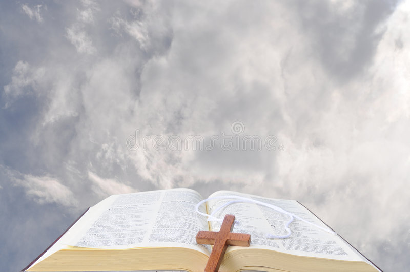 Bible and the heavens. Open bible against the clouds with a wooden cross on it royalty free stock photo