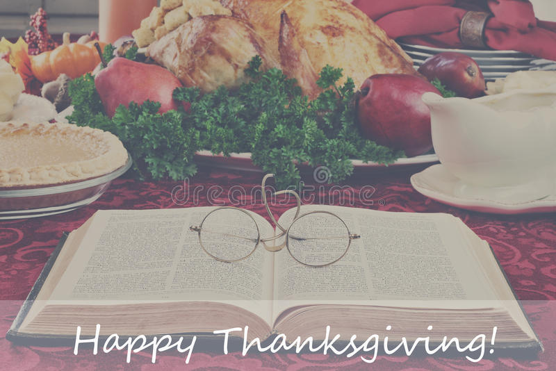 Bible and Holiday Dinner with Happy Thanksgiving Text stock photos