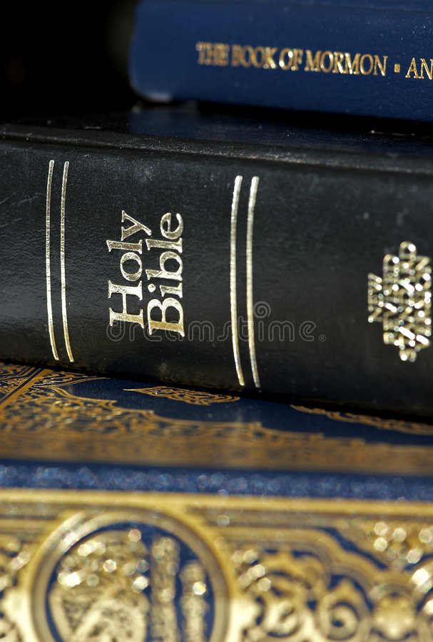 Bible and Koran (Qur'an) and Book of Mormon. Side by side (focus on Bible royalty free stock photography