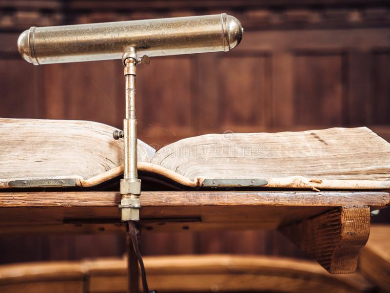 Bible on lectern in church. Opened bible on wooden desk in church, the holy book is illuminated with a lamp royalty free stock photos