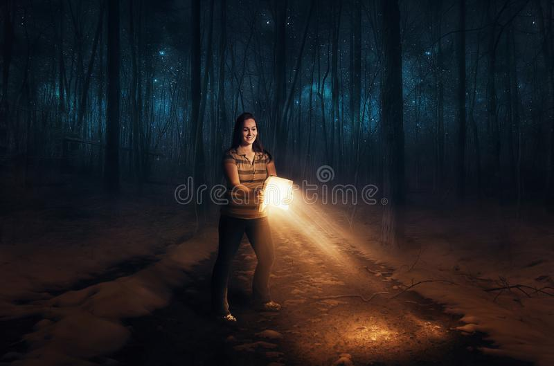 Bible and light. A woman uses a Bible to light her path royalty free stock images
