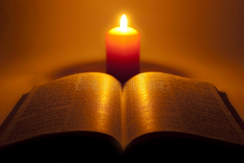 Bible and night candle. stock photos