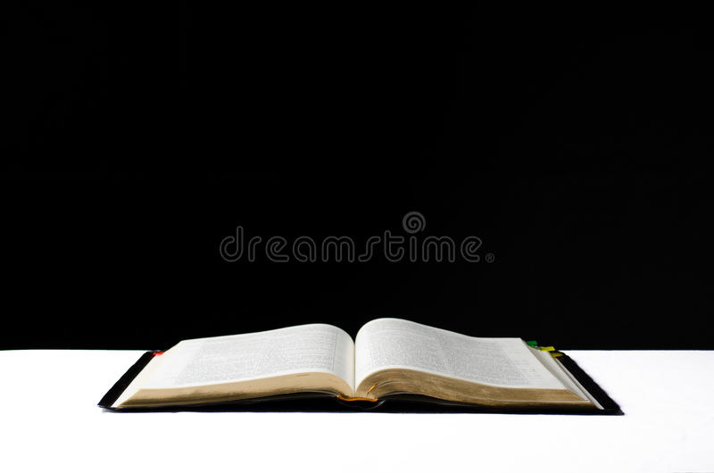 The Bible. Opened Holy Bible on a black background stock photo