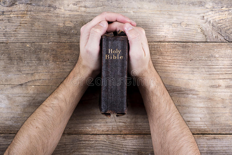 Bible and praying hands. Hands holding Bible on a wooden desk background royalty free stock photos