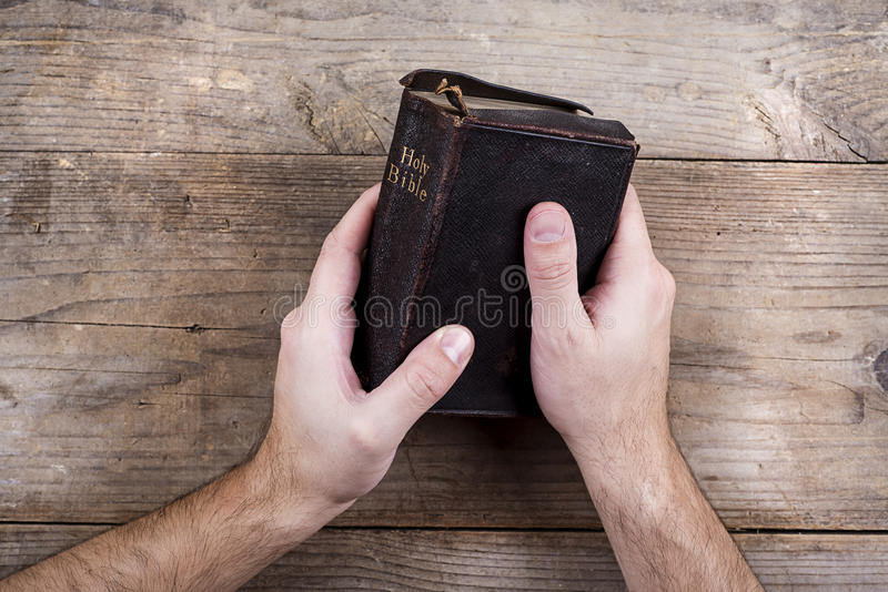 Bible and praying hands. Hands holding Bible on a wooden desk background stock photos
