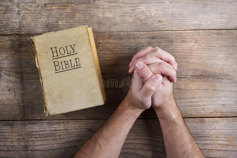 Bible and praying hands. Hands of praying young man and Bible on a wooden desk background royalty free stock photo