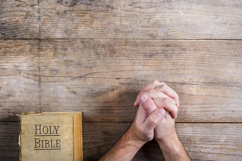 Bible and praying hands. Hands of praying young man and Bible on a wooden desk background stock image