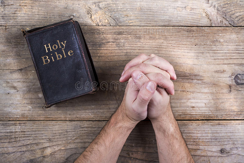 Bible and praying hands. Hands of praying young man and Bible on a wooden desk background royalty free stock image