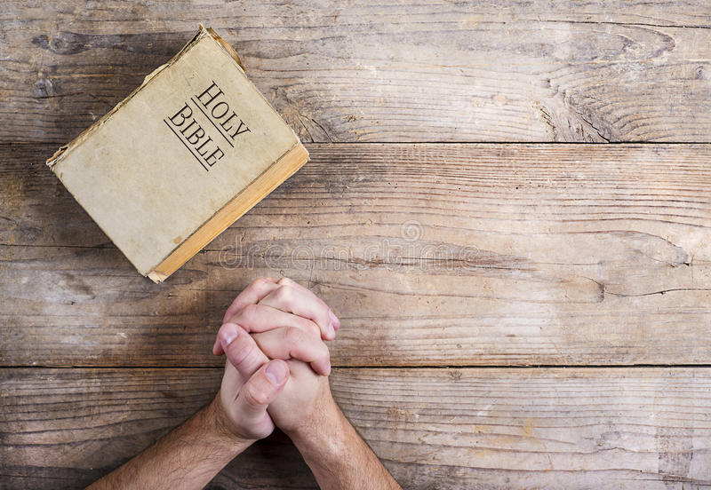 Bible and praying hands stock images