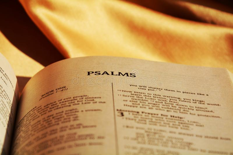 Bible and psalms. The opened Bible on a brown background having the title of psalms focused on, sends to celebrating the Christian religion stock photo