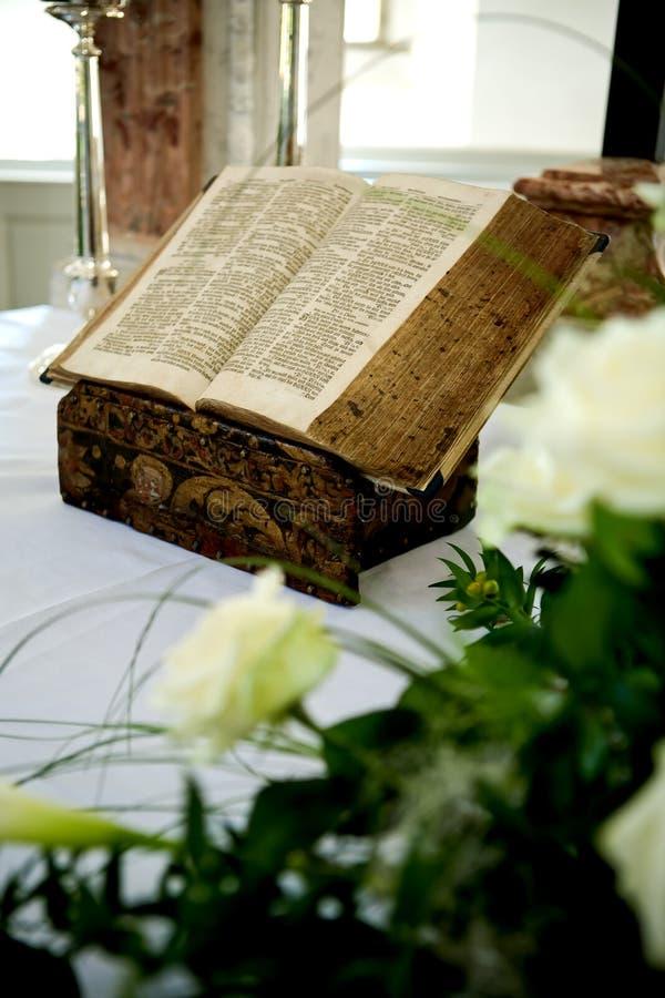 Bible sainte et fleurs sur l'autel dans l'église photographie stock libre de droits