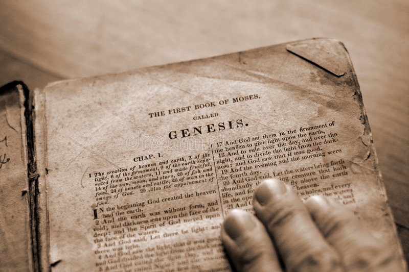 Bible Study. A hand on the bible with page turned to Genesis