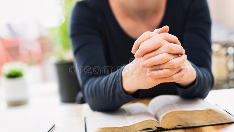 Bible Study and Faith - Woman Praying with an Open Bible. Bible study and faith concept - closeup shot of a woman holding her hands together and praying over an stock photos