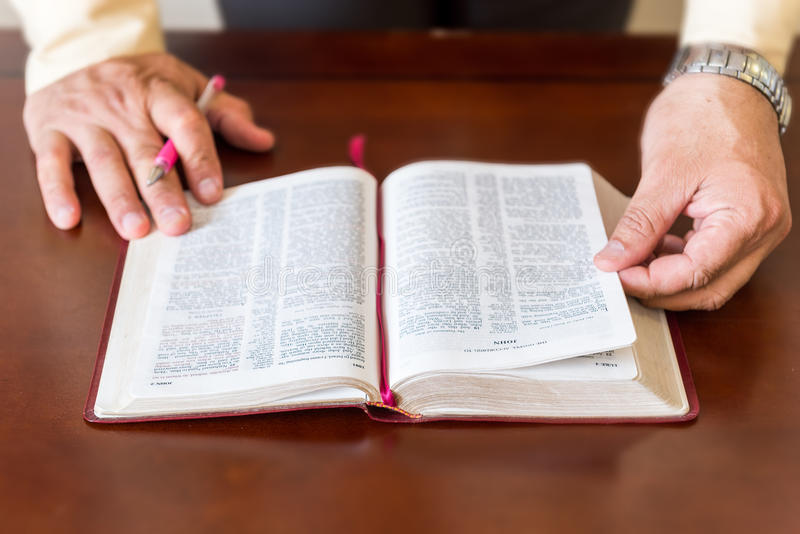 Bible study by a man of God or Pastor. Pastor or man of God reading and teaching the Bible to others and to himself in a small circle or house environment royalty free stock images