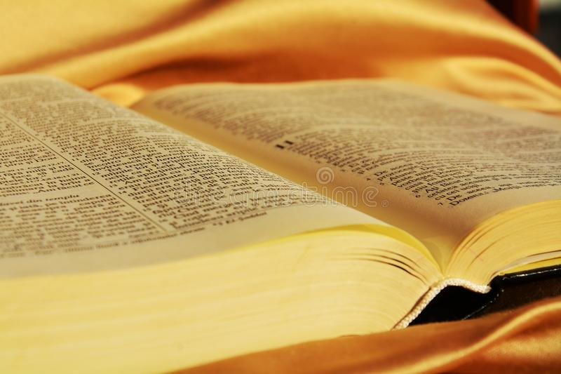 The Bible, symbol of faith. The opened Bible on a golden elegant background reveals the respect the Christians give to its teachings royalty free stock images