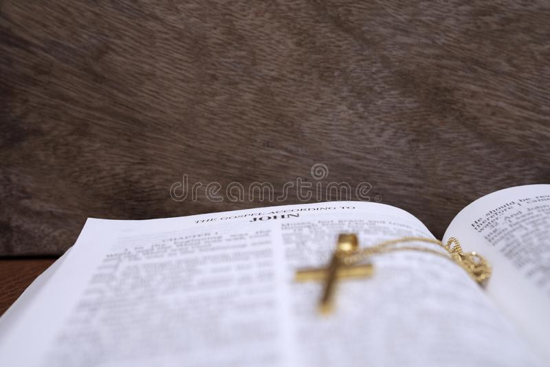 Bible to open at The gospel According to JOHN and  cross for concept inspiration. And empowering royalty free stock image