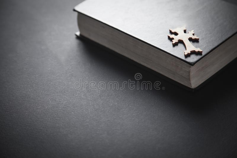 Bible with wooden cross on black background stock image