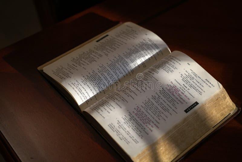 Biblia abierta en una tabla de madera oscura imagen de archivo