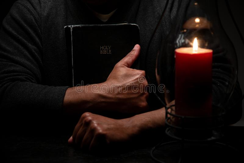 Biblia afroamericana de la tenencia de la persona fotos de archivo