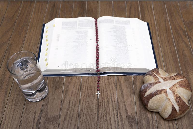 Biblia, chleb i woda na drewnianym stole, obraz stock