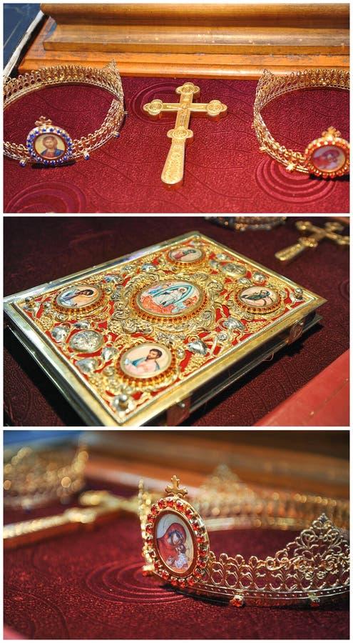 Biblia, cruz, coronas del oro en la tabla en iglesia Celebración de la boda imagen de archivo