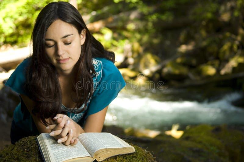 Biblia de la lectura de la mujer joven imagen de archivo