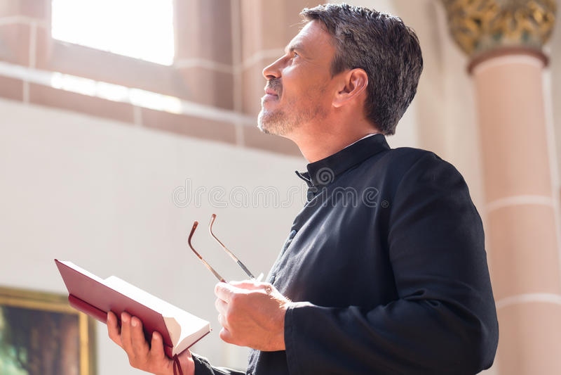 Biblia de la lectura del sacerdote católico en iglesia imagen de archivo