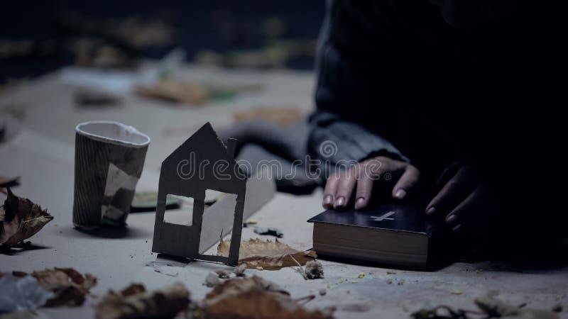 Biblia de la tenencia del refugiado, casa del papel y taza sin hogar cerca, buscando para el hogar fotos de archivo libres de regalías