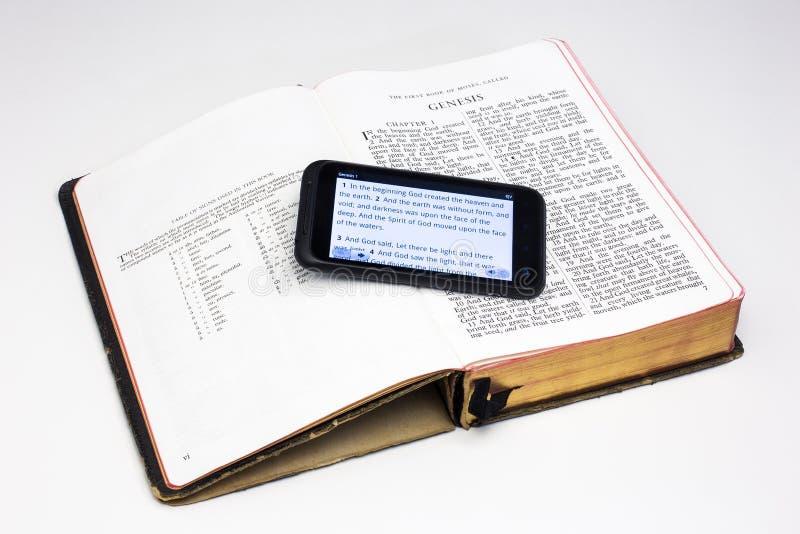 Biblia gastada y Smartphone - génesis fotografía de archivo