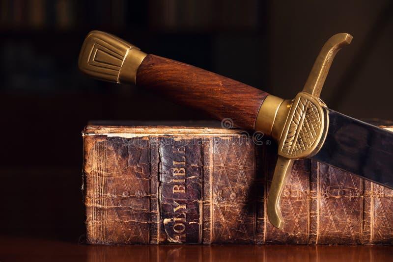Biblia vieja con la espada fotos de archivo