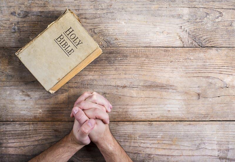 Biblia y manos de rogación imagenes de archivo
