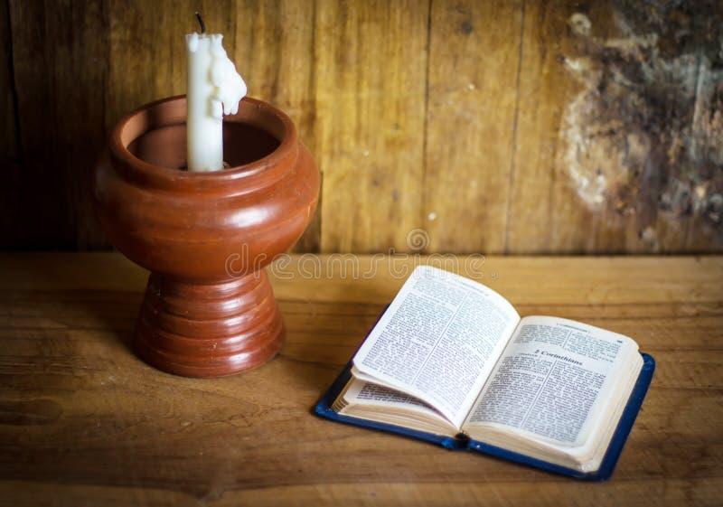 Biblia y velas blancas en la tabla de madera fotografía de archivo libre de regalías