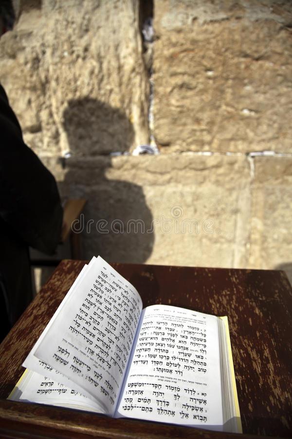 Book of Psalms at the Wailing Wall. The biblical Book of Psalms opened on one of the pages of the morning prayer, resting on a pedistal . There's also a Jewish stock photography