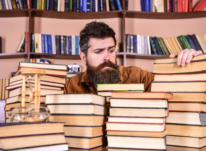 Bibliophile concept. Teacher or student with beard sits at table with books, defocused. Man on hopeful face between. Piles of books, while studying in library stock photography
