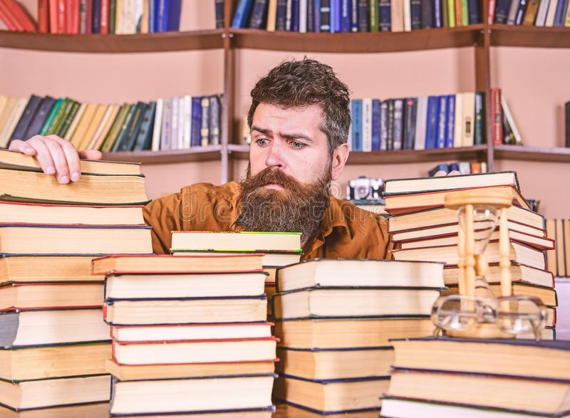Bibliophile concept. Teacher or student with beard sits at table with books, defocused. Man on hopeful face between. Piles of books, while studying in library royalty free stock photography
