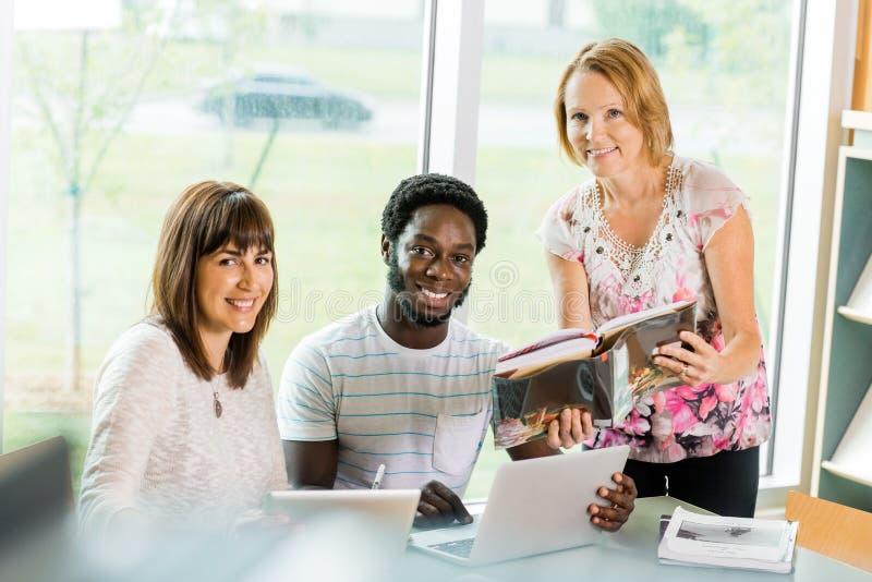 Bibliotecário Assisting College Students na biblioteca imagem de stock