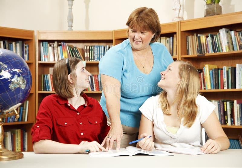 Bibliotecário e estudantes adolescentes imagens de stock royalty free