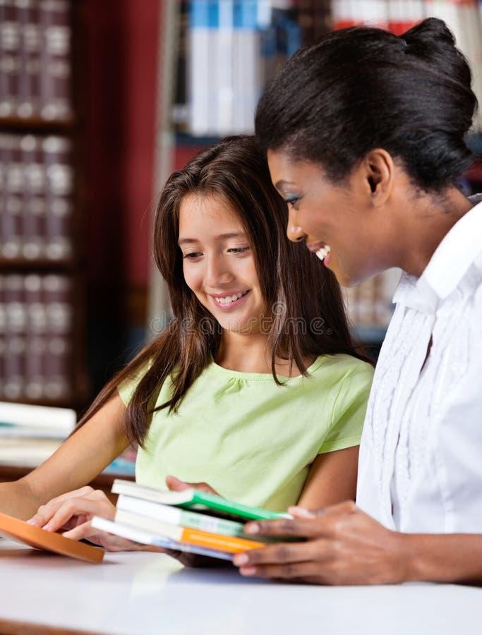 Bibliotecário And Schoolgirl Looking junto no livro imagens de stock royalty free