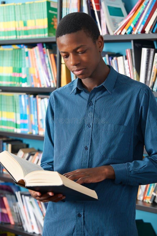 Biblioteca adolescente maschio di Reading Book In dello studente immagini stock