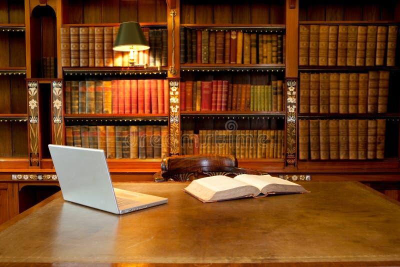 Biblioteca, computador e mesa