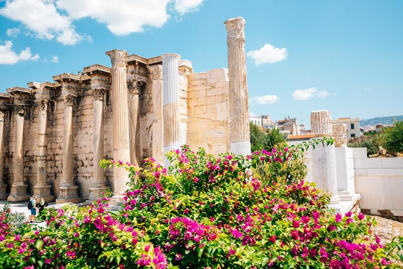 Biblioteca de Hadrian ruínas antigas com flores em Atenas, Grécia fotos de stock royalty free