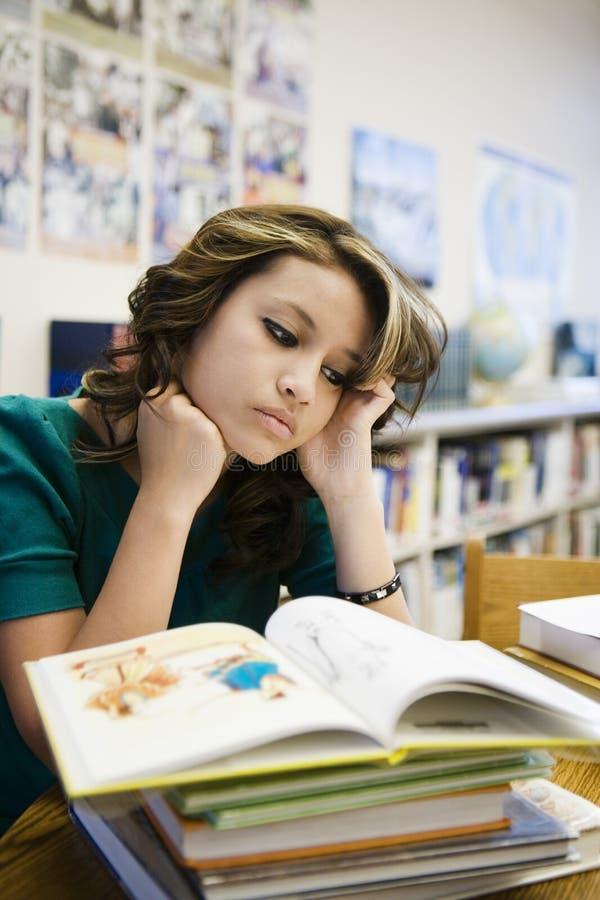 Biblioteca de Reading Book In do estudante fêmea imagem de stock