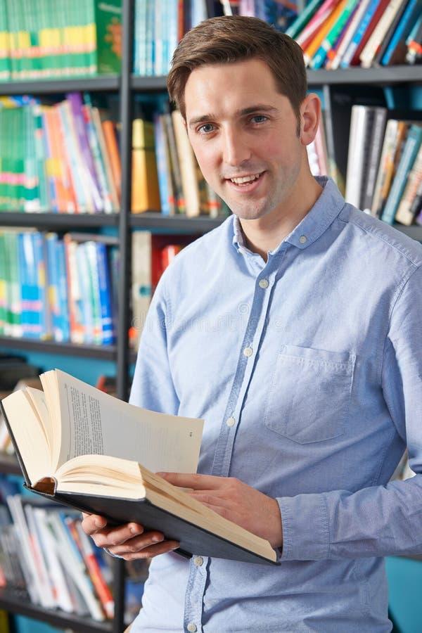 Biblioteca de Reading Textbook In del estudiante universitario foto de archivo libre de regalías