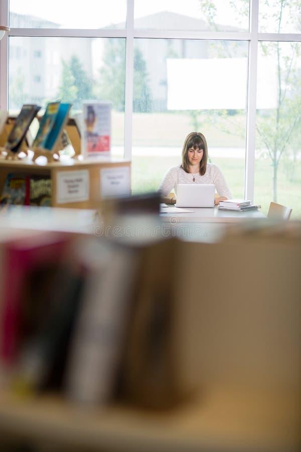 Biblioteca de Using Laptop In do estudante foto de stock