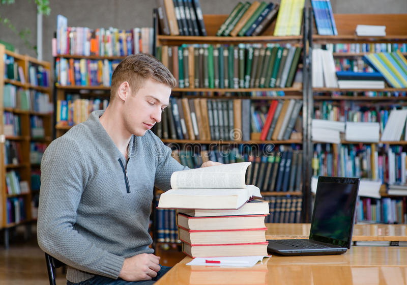 Biblioteca di Reading Book In dello studente maschio fotografia stock