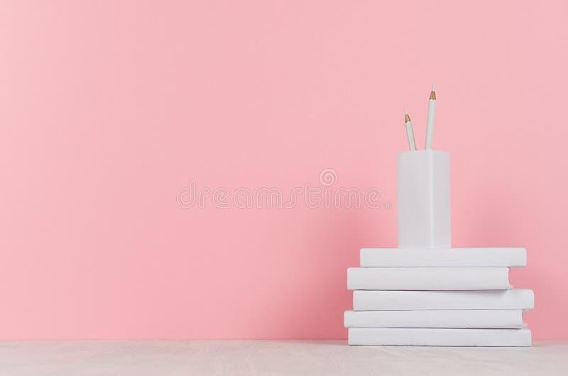 Biblioteca di scuola creativa - accatasti i libri in bianco bianchi e le matite bianche su fondo rosa immagine stock