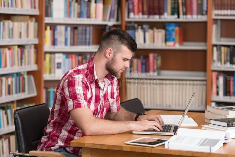 Biblioteca feliz de With Laptop In del estudiante masculino fotos de archivo libres de regalías