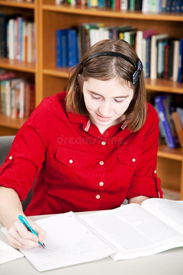 Biblioteca - pesquisa adolescente da menina fotografia de stock