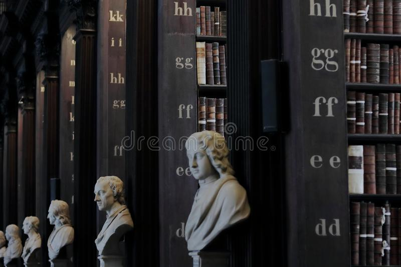 Biblioteca vieja con los libros y las esculturas históricos imágenes de archivo libres de regalías